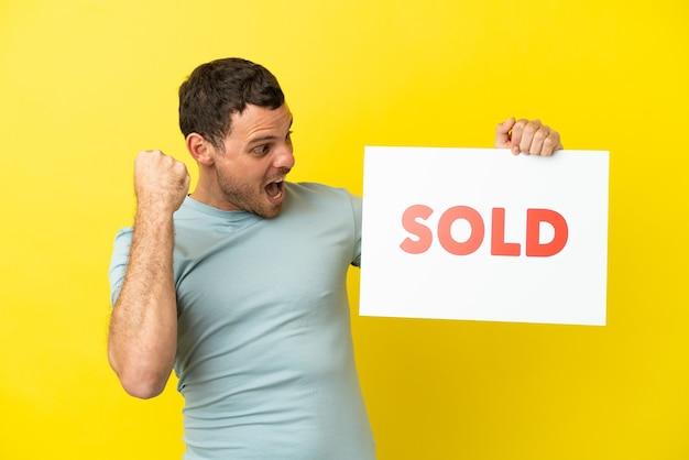 Braziliaanse man over geïsoleerde paarse achtergrond met een bordje met tekst verkocht en een overwinning vieren