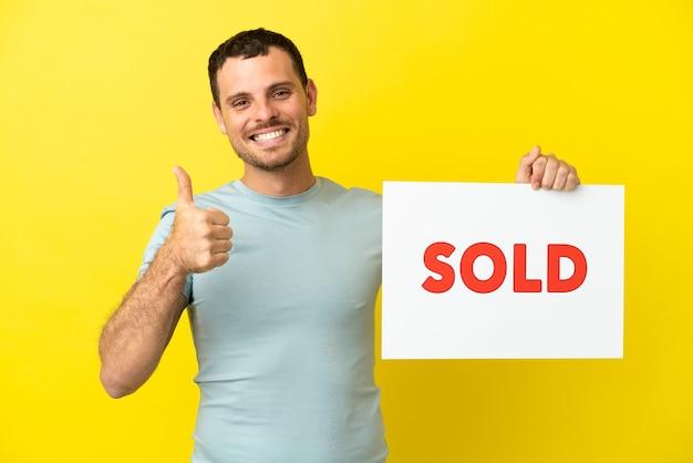 Braziliaanse man over geïsoleerde paarse achtergrond met een bordje met tekst verkocht met duim omhoog