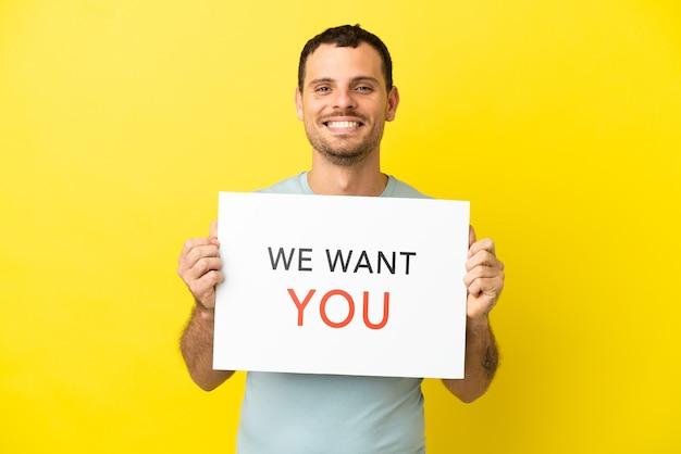 Braziliaanse man over geïsoleerde paarse achtergrond met we want you-bord met gelukkige uitdrukking
