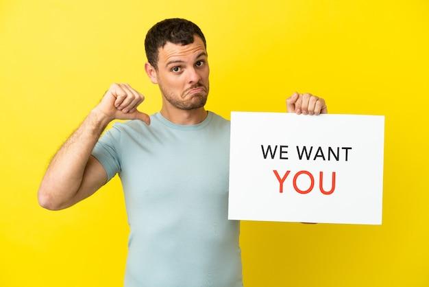 Braziliaanse man over geïsoleerde paarse achtergrond met we want you-bord met trots gebaar