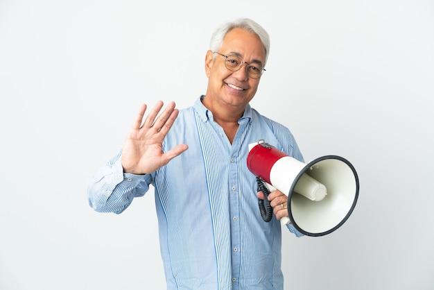 Braziliaanse man van middelbare leeftijd geïsoleerd op een witte achtergrond die een megafoon vasthoudt en met de hand salueert met een gelukkige uitdrukking