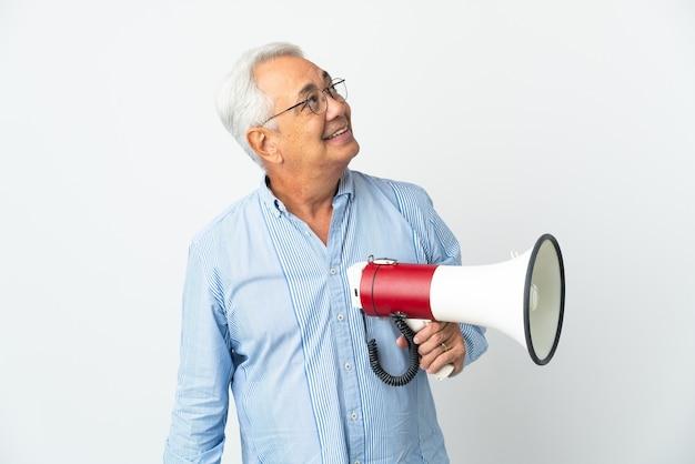 Braziliaanse man van middelbare leeftijd geïsoleerd op een witte achtergrond die een megafoon vasthoudt en omhoog kijkt terwijl hij glimlacht