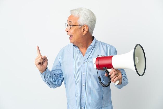 Braziliaanse man van middelbare leeftijd geïsoleerd op een witte achtergrond die een megafoon vasthoudt en van plan is de oplossing te realiseren