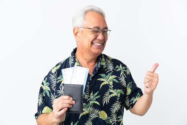 Braziliaanse man van middelbare leeftijd geïsoleerd op een witte achtergrond in vakantie met een paspoort en vliegtuig met duim omhoog