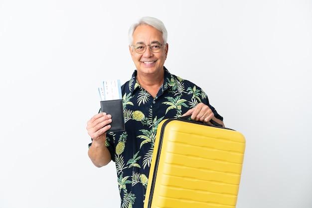 Braziliaanse man van middelbare leeftijd geïsoleerd op een witte achtergrond in vakantie met koffer en paspoort