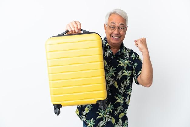 Braziliaanse man van middelbare leeftijd geïsoleerd op een witte achtergrond in vakantie met reiskoffer