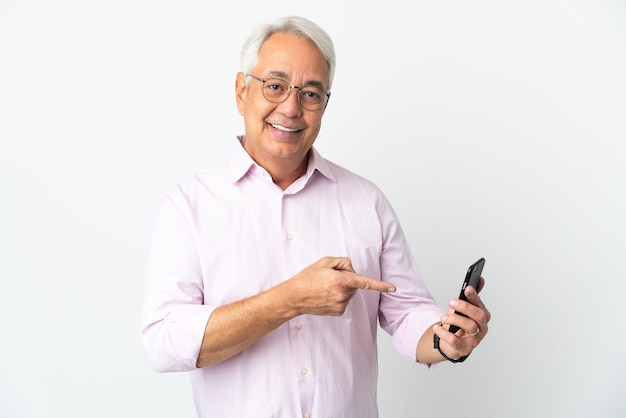 Braziliaanse man van middelbare leeftijd geïsoleerd op een witte achtergrond met behulp van mobiele telefoon en wijzend