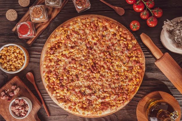 Braziliaanse pizza met mozzarela, maïs, spek en oregano (pizza de milho com bacon) - bovenaanzicht.