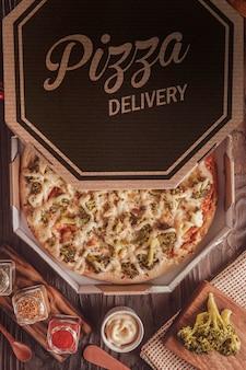 Braziliaanse pizza met mozzarella, broccoli, catupiry en parmezaan in een bezorgdoos (pizza de brocolis) - bovenaanzicht.