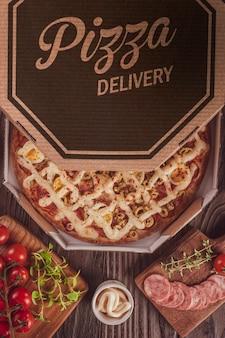 Braziliaanse pizza met mozzarella, calabrese worst, eieren, catupiry, olijven en oregano in een bezorgdoos (pizza especial de calabresa) - bovenaanzicht.