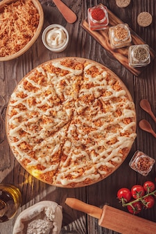 Braziliaanse pizza met mozzarella, kip, catupiry en oregano (pizza de frango com catupiry) - bovenaanzicht.
