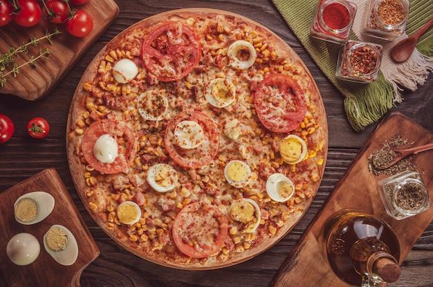 Braziliaanse pizza met mozzarella, maïs, spek, eieren, tomaat en oregano (pizza especial) - bovenaanzicht.