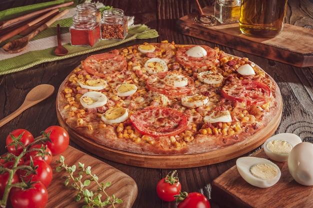 Braziliaanse pizza met mozzarella, mais, spek, eieren, tomaat en oregano (pizza speciaal)