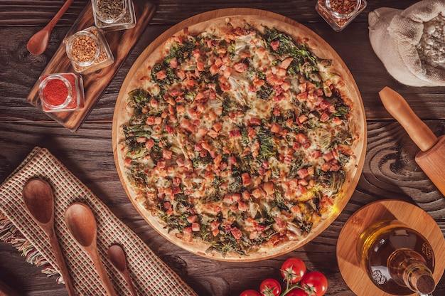Braziliaanse pizza met tomatensaus, mozzarella, andijvie, spek en oregano (pizza de escarola com bacon) - bovenaanzicht.