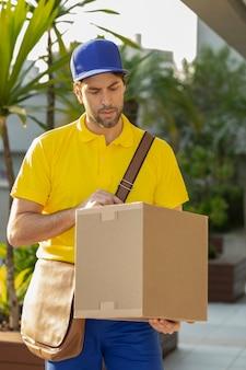 Braziliaanse postbode die een pakket op straat aflevert. aankoop via internet wordt thuis afgeleverd.