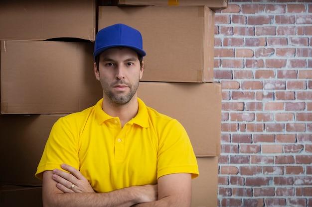 Braziliaanse postbode met gekruiste armen in een depot met veel dozen.
