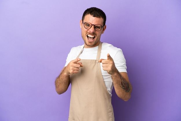Braziliaanse restaurantkelner over geïsoleerde paarse achtergrond die naar voren wijst en glimlacht