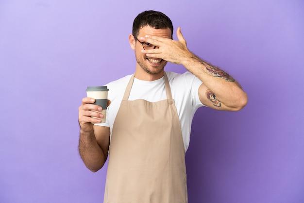 Braziliaanse restaurantkelner over geïsoleerde paarse achtergrond die ogen bedekt door handen en glimlacht