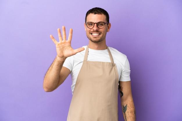 Braziliaanse restaurantkelner over geïsoleerde paarse achtergrond die vijf met vingers telt