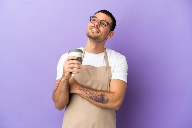 Braziliaanse restaurantkelner over geïsoleerde paarse achtergrond terwijl hij glimlacht