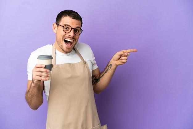 Braziliaanse restaurantkelner over geïsoleerde paarse achtergrond verrast en wijzende vinger naar de zijkant?