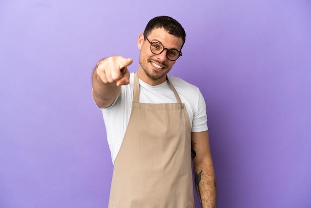Braziliaanse restaurantkelner over geïsoleerde paarse achtergrond wijst naar je met een zelfverzekerde uitdrukking