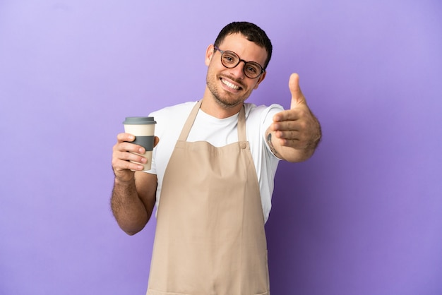 Braziliaanse restaurantkelner over geïsoleerde paarse muur die handen schudt voor het sluiten van een goede deal