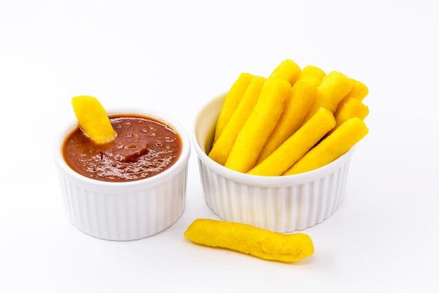 Braziliaanse snack genaamd polenta, geserveerd met saus en ketchup, geïsoleerd wit oppervlak.