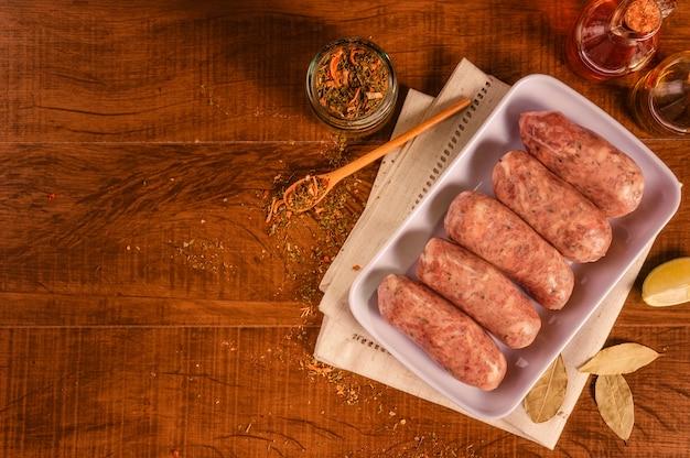 Braziliaanse varkensworst met chimichurri op witte plaat met kruiden en ingrediënten