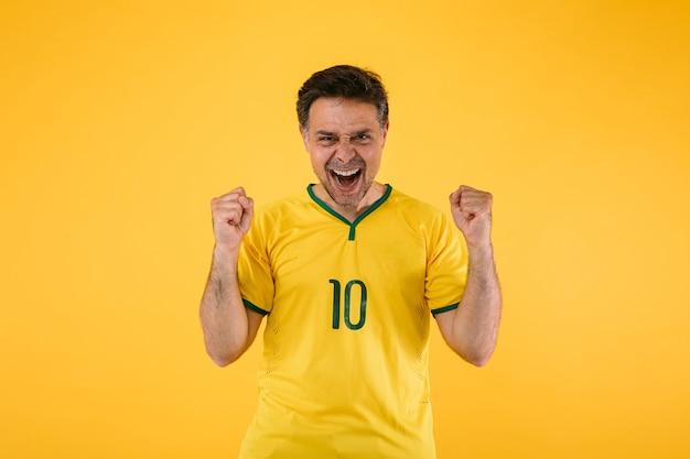 Braziliaanse voetbalfan in een gele trui balt zijn vuisten en schreeuwt juichend voor zijn team.