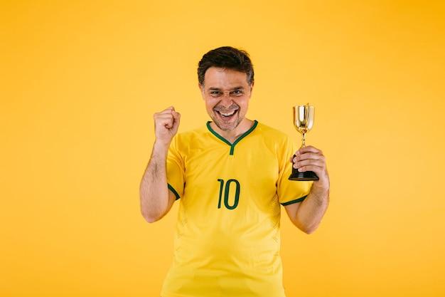 Braziliaanse voetbalfan in een gele trui, hij balt zijn vuist en houdt een winnaarstrofee vast.