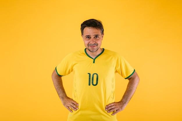 Braziliaanse voetbalfan in geel shirt, poseert met armen op taille