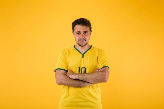 Braziliaanse voetbalfan in gele trui poseert met gekruiste armen