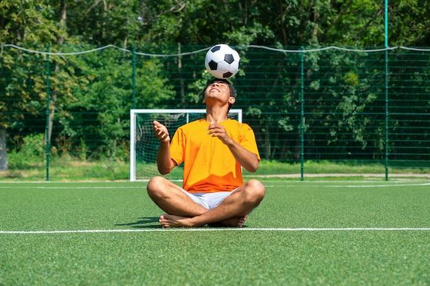 Braziliaanse voetballer traint en verbetert de balcontrole door hem in de zomer op zijn hoofd te jongleren terwijl hij op het sportveld zit