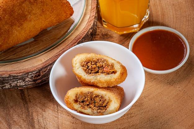 Braziliaanse voorgerecht gefrituurde rundvleeskroket met pepersaus en sinaasappelsap