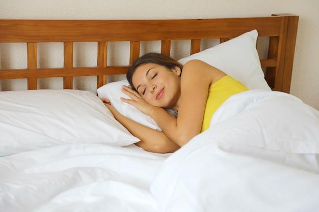 Braziliaanse vrouw slapen in bed in witte comfortabele lakens thuis