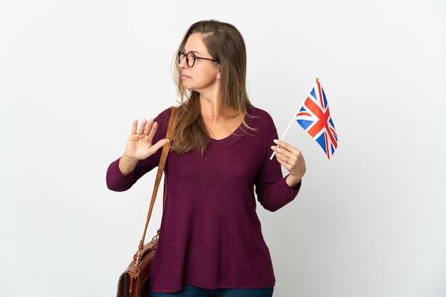 Braziliaanse vrouw van middelbare leeftijd die een vlag van het verenigd koninkrijk houdt die op witte muur wordt geïsoleerd die eindegebaar maakt en teleurgesteld