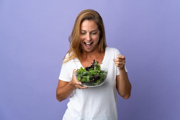 Braziliaanse vrouw van middelbare leeftijd die op het houden van een kom salade met gelukkige uitdrukking wordt geïsoleerd