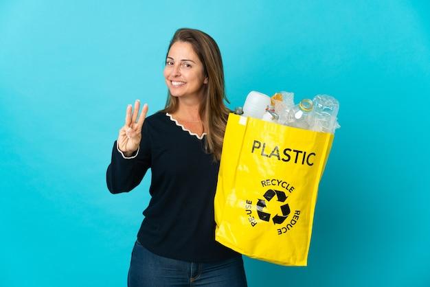 Braziliaanse vrouw van middelbare leeftijd met een zak vol plastic flessen om te recyclen op een blauwe muur, gelukkig en drie tellen met vingers
