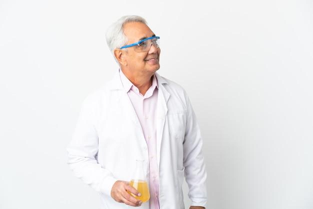 Braziliaanse wetenschappelijke man van middelbare leeftijd wetenschappelijk geïsoleerd op een witte achtergrond die een idee denkt terwijl hij omhoog kijkt