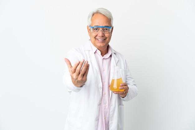 Braziliaanse wetenschappelijke man van middelbare leeftijd wetenschappelijk geïsoleerd op een witte achtergrond die uitnodigt om met de hand te komen. blij dat je gekomen bent