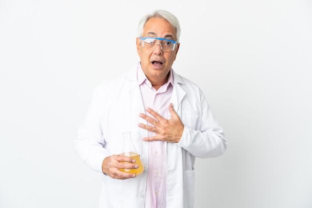 Braziliaanse wetenschappelijke man van middelbare leeftijd wetenschappelijk geïsoleerd op een witte achtergrond verrast en geschokt terwijl hij er goed uitziet