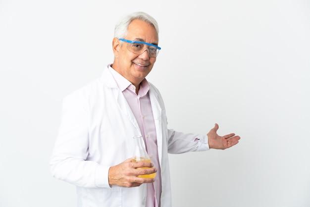Braziliaanse wetenschappelijke man van middelbare leeftijd wetenschappelijk geïsoleerd op een witte muur die de handen uitstrekt naar de zijkant om uit te nodigen om te komen