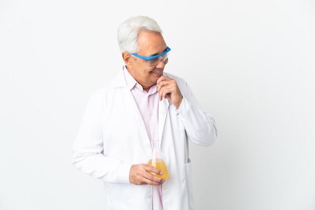 Braziliaanse wetenschappelijke man van middelbare leeftijd wetenschappelijk geïsoleerd op een witte muur op zoek naar de zijkant en glimlachen