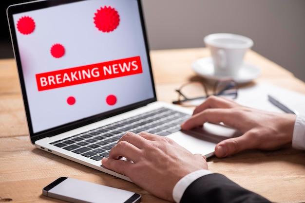 Breaking news, coronavirus of covid-19 uitbraak. man die een notebook gebruikt om nieuws te lezen