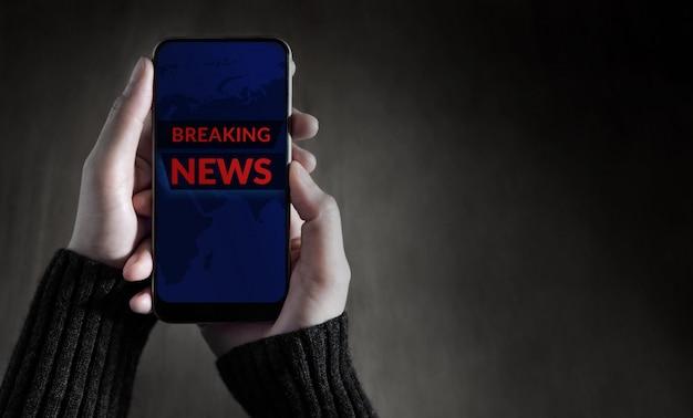 Breaking news headline weergegeven op het scherm van mobile. persoon die een smartphone gebruikt om nieuws en updates te controleren. bovenaanzicht