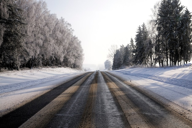 Brede asfaltweg in het winterseizoen