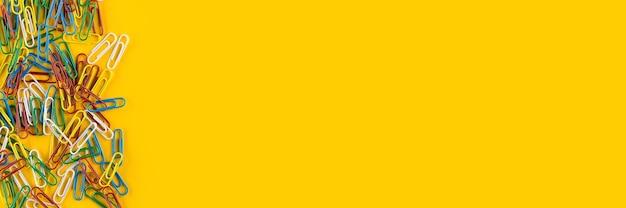 Brede banner. bos van kleurrijke paperclips op gele achtergrond. creatieve plat lag terug naar school concept op helder geel papier achtergrond met kopie ruimte.