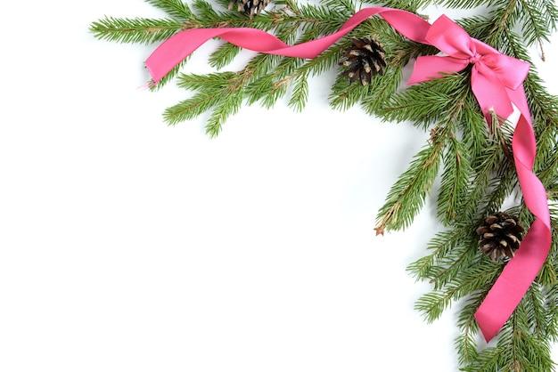 Brede boogvormige kerstgrens geïsoleerd op wit, samengesteld uit verse dennentakken, kegels en lintboog