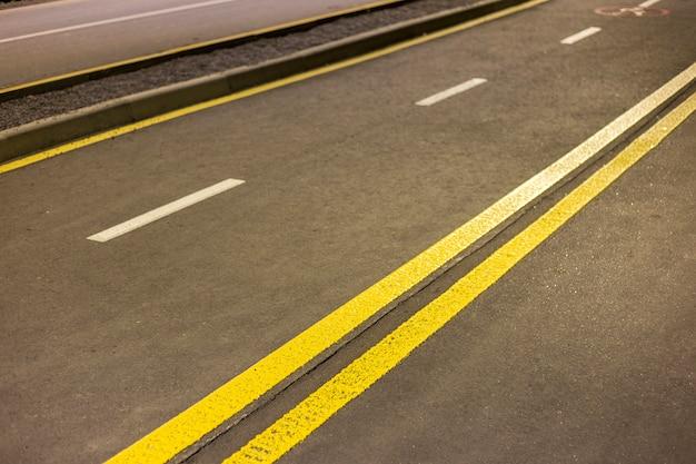 Brede heldere dubbele gele markering teken lijn langs moderne brede gladde lege asfalt snelweg straat die zich uitstrekt tot horizon. snelheid, veiligheid, comfortabele reis en professioneel wegenbouwconcept.